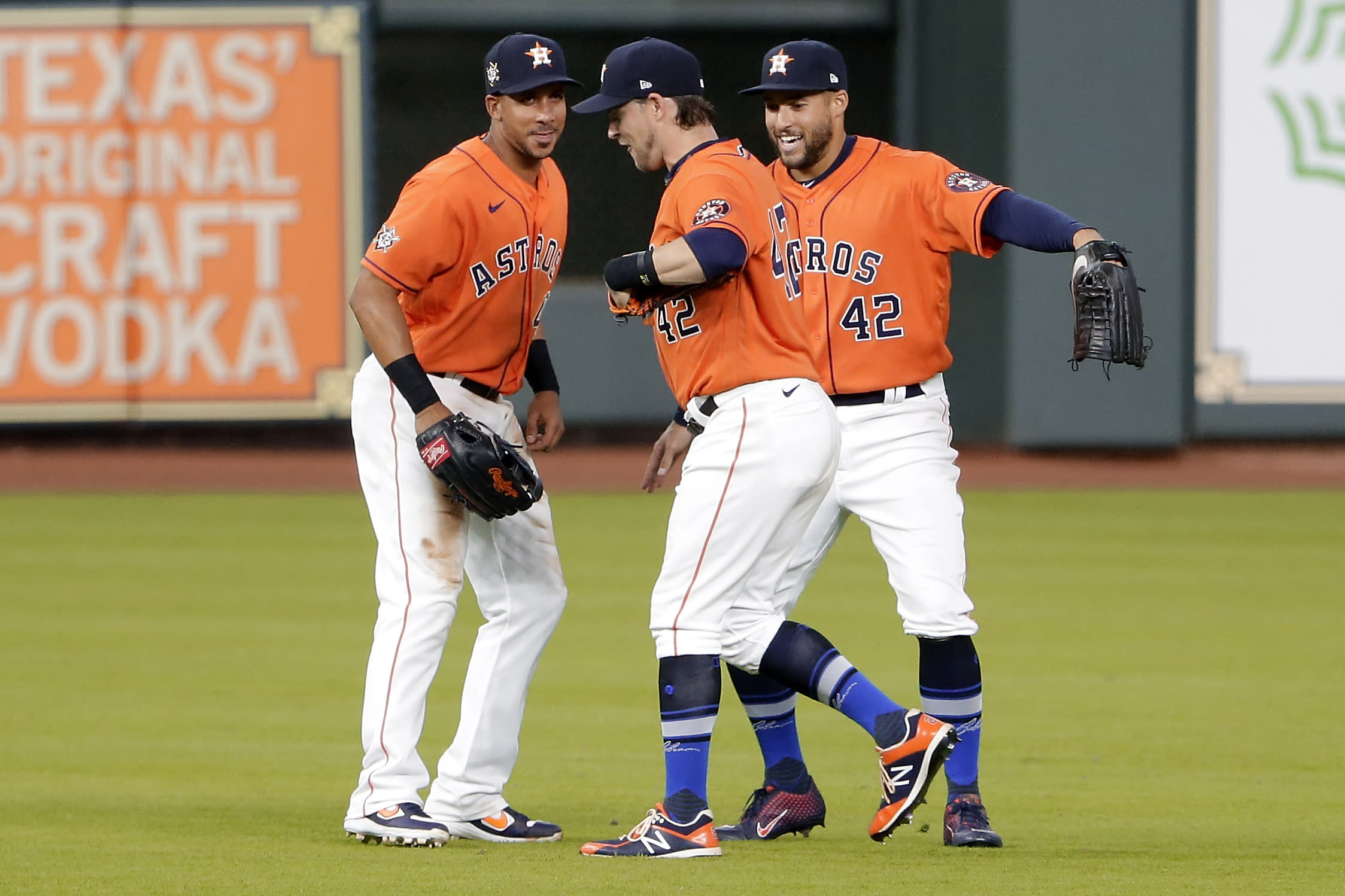 Houston Astros outfielders Michael Brantley, left, Josh Reddick, center, and George Springer, right, celebrate their win over the Oakland Athletics after the first baseball game of a doubleheader Saturday, Aug. 29, 2020, in Houston. All players and managers are wearing No. 42 as a tribute to baseball great Jackie Robinson. (AP Photo/Michael Wyke)