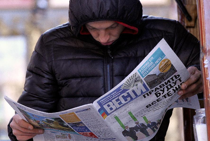 A man reads a newspaper bearing headlines on the results of the Ukrainian parliamentary elections, on October 27, 2014 in Kiev (AFP Photo/Sergei Gapon)