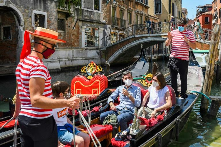 The Venice gondoliers are back in business after Italy eased its virus lockdown, but can now only take on board five passengers at a time (AFP Photo/ANDREA PATTARO)