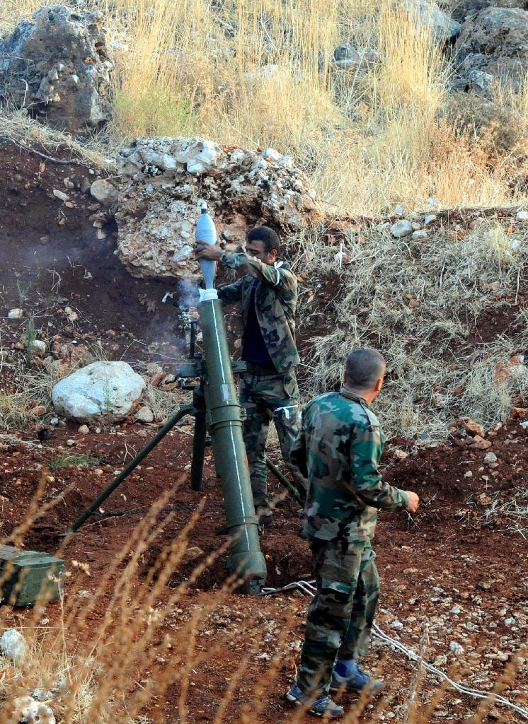 A handout picture released by the official Syrian Arab News Agency (SANA), shows pro-government forces firing mortar rounds at an undisclosed location in western Syria on October 8, 2015 (AFP Photo/)