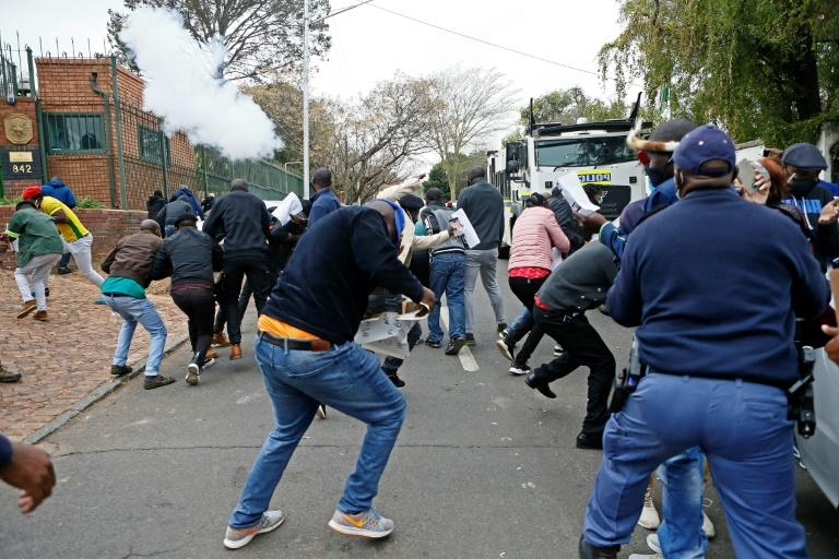 Protesters run from a stun grenade fired by police outside the Zimbabwean Embassy in South Africa's Pretoria