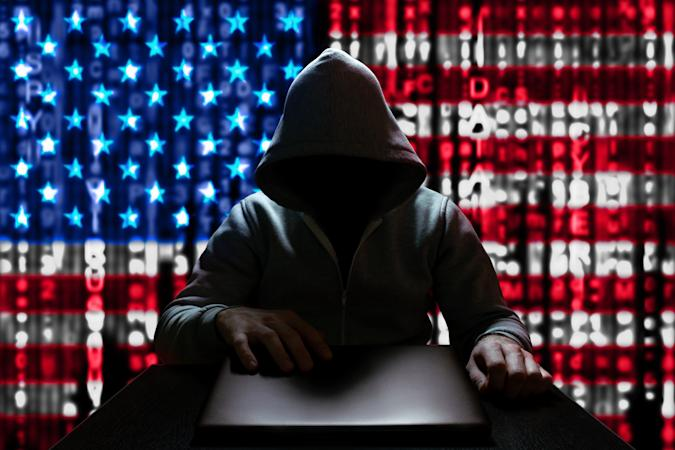 Cyberattack from the USA. An American hacker turns on a laptop, sitting at a table, on a background of binary code, the colors of the USA flag. DDoS attack