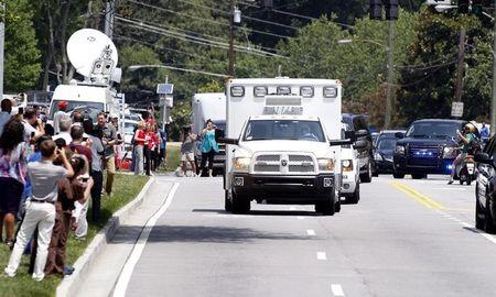 An ambulance carrying a second American aid worker infected with Ebola in West Africa arrives past crowds of people taking pictures at Emory University Hospital in Atlanta