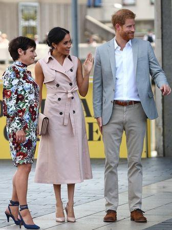 Britain's Meghan, the Duchess of Sussex, and Prince Harry, accompanied by Elaine Bedell, Chief Executive of Southbank Centre, wave at well-wishers as they arrive at the Nelson Mandela Centenary Exhibition at the Southbank Centre's Queen Elizabeth Hall in central London, Britain, July 17, 2018. REUTERS/Hannah McKay