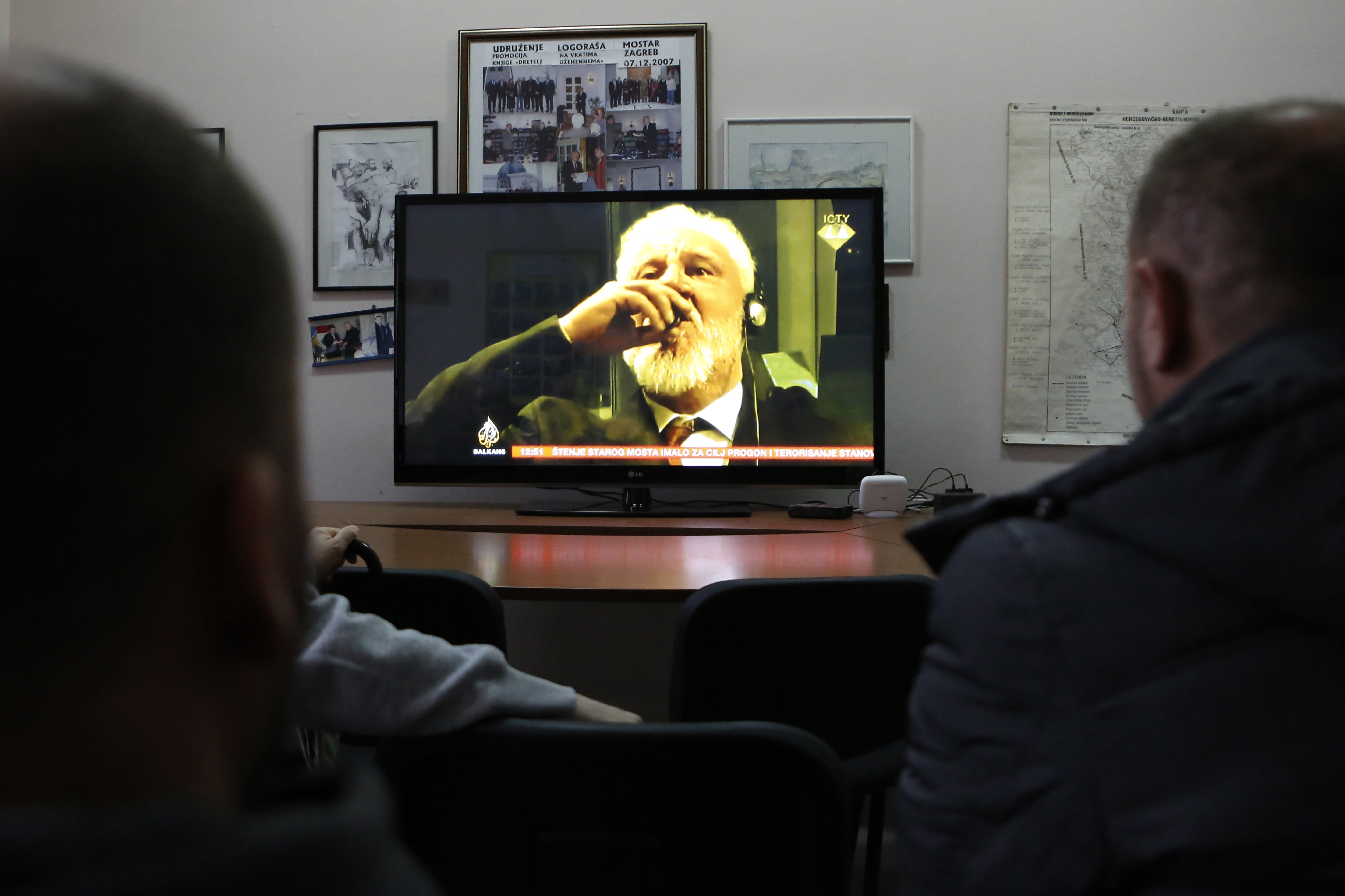 """FILE - In this Wednesday, Nov. 29, 2017 file photo, Bosnian people watch the live TV broadcast from the International Criminal Court for the former Yugoslavia (ICTY) in The Hague as Slobodan Praljak brings a bottle to his lips, in southern Bosnian town of Mostar 140 kms south of Sarajevo. Julian Assange relayed how he """"binge-watched"""" the suicide of the former Bosnian Croat general in a United Nations courtroom three years ago, a doctor who visited the WikiLeaks founder on several occasions while he was in the Ecuadorian Embassy in London told an extradition hearing Thursday, Sept, 24, 2020. (AP Photo/Amel Emric, file)"""