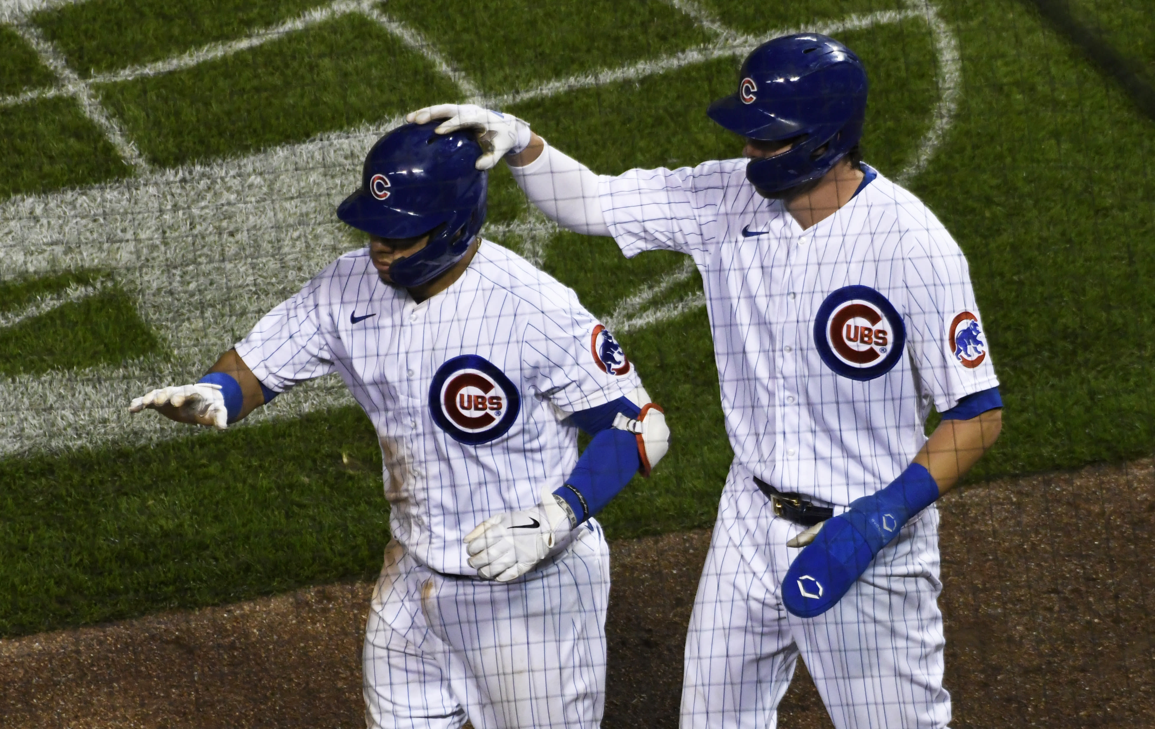 Chicago Cubs' Kris Bryant, right, pats Willson Contreras, left, on the helmet after Contreras drove in Bryant on a RBI sacrifice fly against the Cleveland Indians during the seventh inning of a baseball game, Tuesday, Sept.15, 2020, in Chicago. (AP Photo/David Banks)