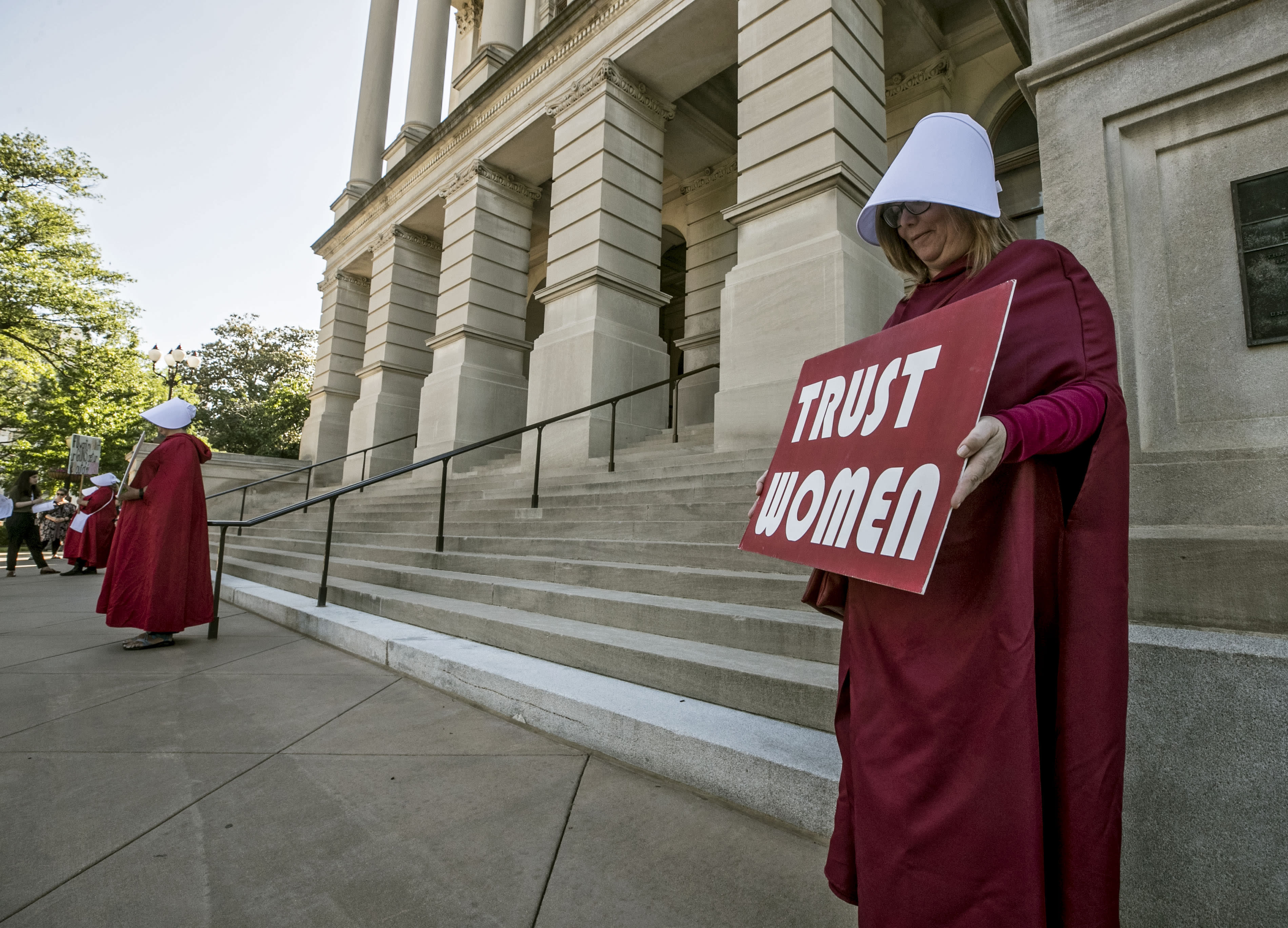 "File-Michelle Disher, from Roswell, and others dressed as characters from ""The Handmaid's Tale"", protest outside the Capitol where Georgia's Republican Gov. Brian Kemp, was to sign the legislation, Tuesday, May 7, 2019, in Atlanta, banning abortions once a fetal heartbeat can be detected, which can be as early as six weeks before many women know they're pregnant. A federal judge is permanently blocking Georgia's 2019 ""heartbeat"" abortion law, finding that it violates the U.S. Constitution. U.S. District Judge Steve Jones ruled against the state Monday, July 13, 2020, in a lawsuit filed by abortion providers and an advocacy group. (Bob Andres/Atlanta Journal-Constitution via AP, File)"