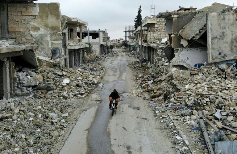A man rides a motorbike through the almost-deserted town of Kafranbel on February 15, just days before its capture by the regime