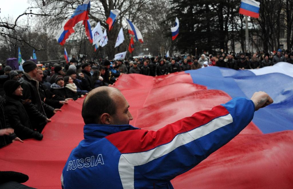 Pro-Russian demonstrators carry a giant Russian flag as they rally in central Simferopol on February 27, 2014