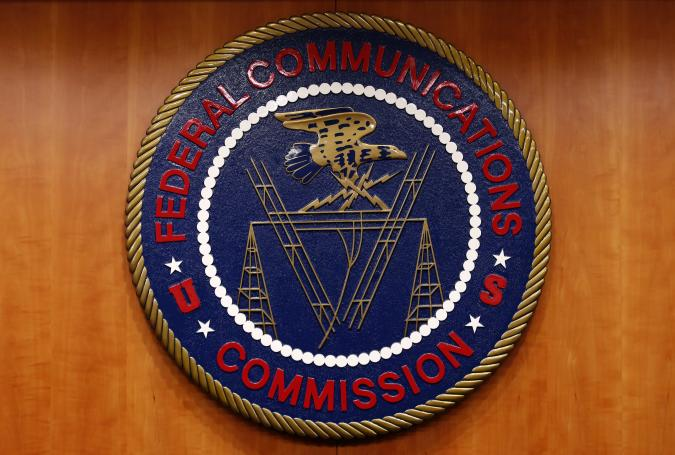 """The Federal Communications Commission (FCC) logo is seen before the FCC Net Neutrality hearing in Washington February 26, 2015. The FCC is expected Thursday to approve Chairman Tom Wheeler's proposed """"net neutrality"""" rules, regulating broadband providers more heavily than in the past and restricting their power to control download speeds on the web. REUTERS/Yuri Gripas (UNITED STATES - Tags: POLITICS SCIENCE TECHNOLOGY BUSINESS TELECOMS LOGO)"""