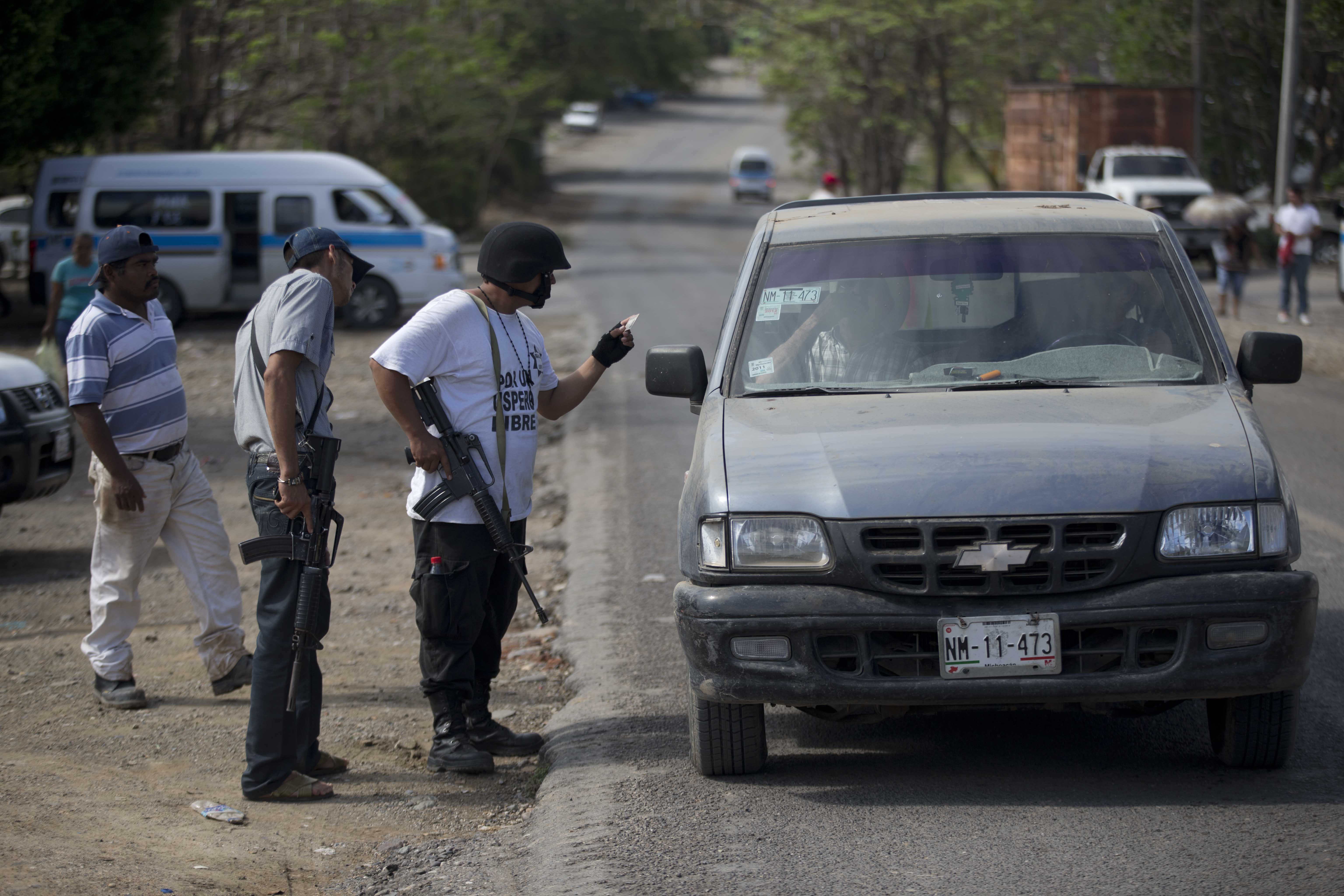 Armed men belonging to the Self-Defense Council of Michoacan (CAM) check the documents of people in a vehicle at a checkpoint set up by the vigilante group in La Mira on the outskirts of the seaport of Lazaro Cardenas in western Mexico, Friday, May 9, 2014. A ceremony on Saturday will mark the registering of thousands of guns by the federal government and an agreement that the self-defense groups will either join a new official rural police force or return to their normal lives and act as voluntary reserves when called on. But tension remained on Friday in the coastal part of the state outside the port of Lazaro Cardenas, where some self-defense groups plan to continue as they are, defending their territory without registering their arms. (AP Photo/Eduardo Verdugo)