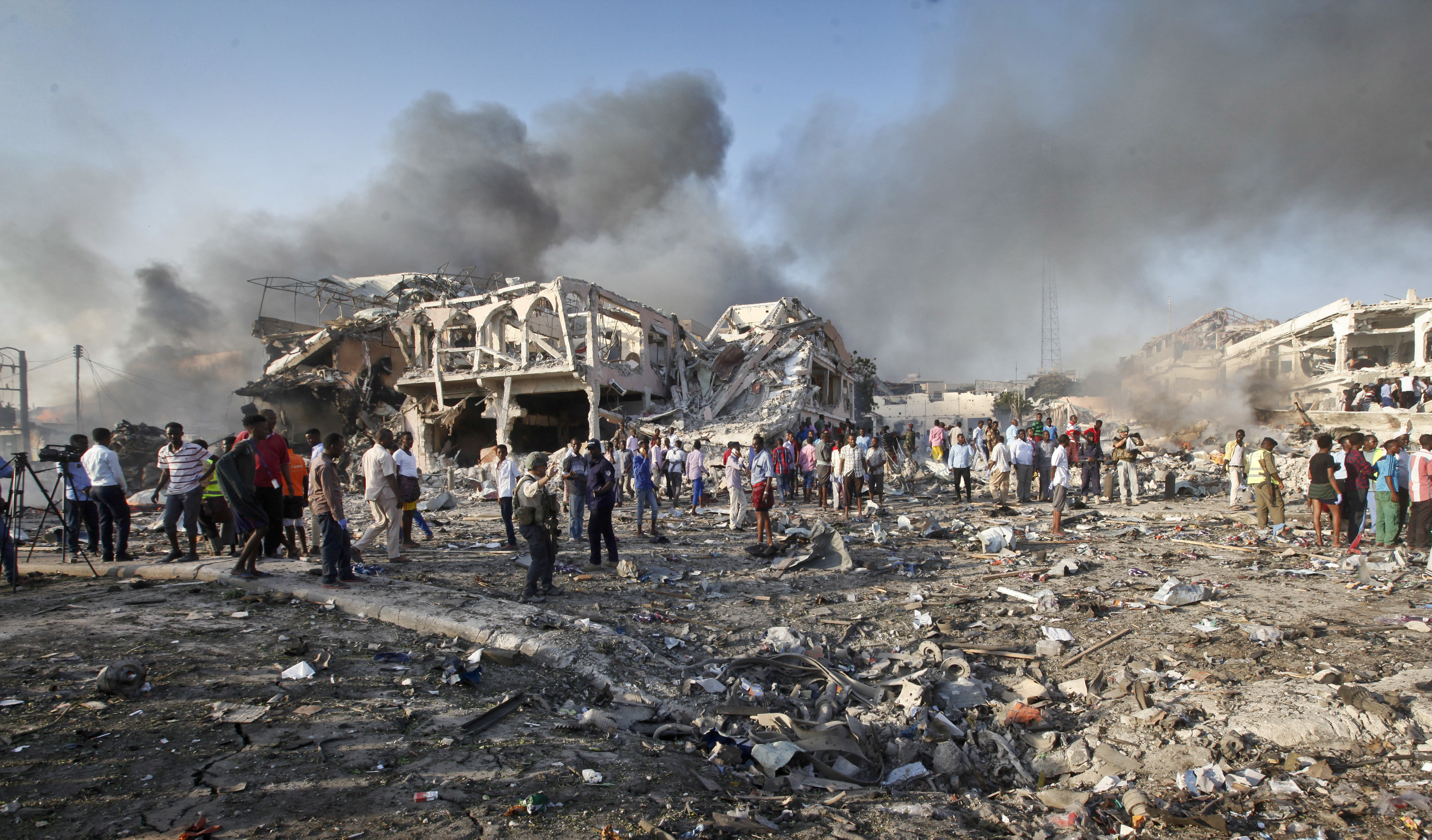 FILE - In this Saturday, Oct. 14, 2017 file photo, Somalis gather and search for survivors by destroyed buildings at the scene of a blast in the capital Mogadishu, Somalia. The U.S. Africa Command, signaling concern over the Pentagon's potential cuts in a briefing, has emphasized the Somalia-based al-Shabab as a threat to the U.S. homeland, in intent if not yet in capability _ and warning that neither China nor Russia is doing much to counter Africa's extremist groups.(AP Photo/Farah Abdi Warsameh, File)