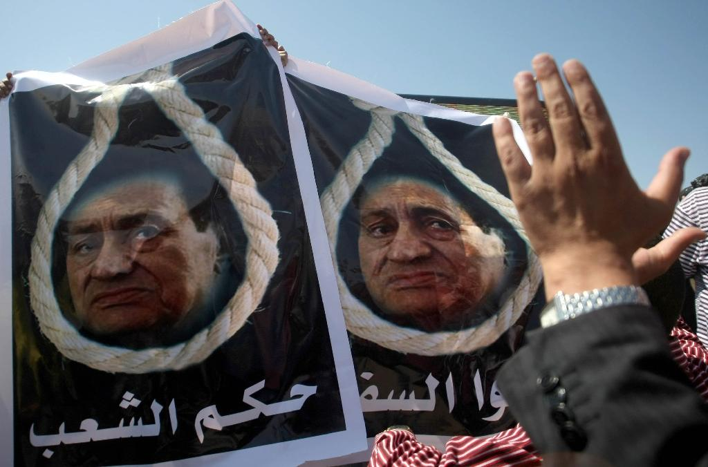 Posters show Egypt's ousted president Hosni Mubarak in a noose on August 3, 2011 outside a hearing in his trial in the Cairo Police Academy