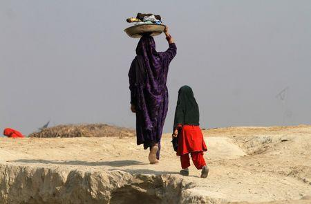 A woman carries laundry on her head, while heading home after washing in Charsadda, near Peshawar