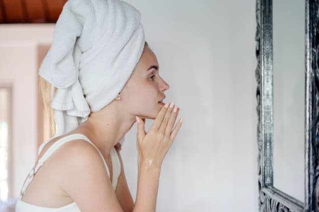 Young adult female standing in white bathroom with towel on head