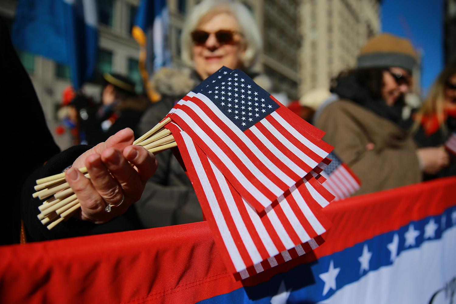 <p>A woman holds flags for the Veterans Day parade in New York on Nov. 11, 2018. (Photo: Gordon Donovan/Yahoo News) </p>