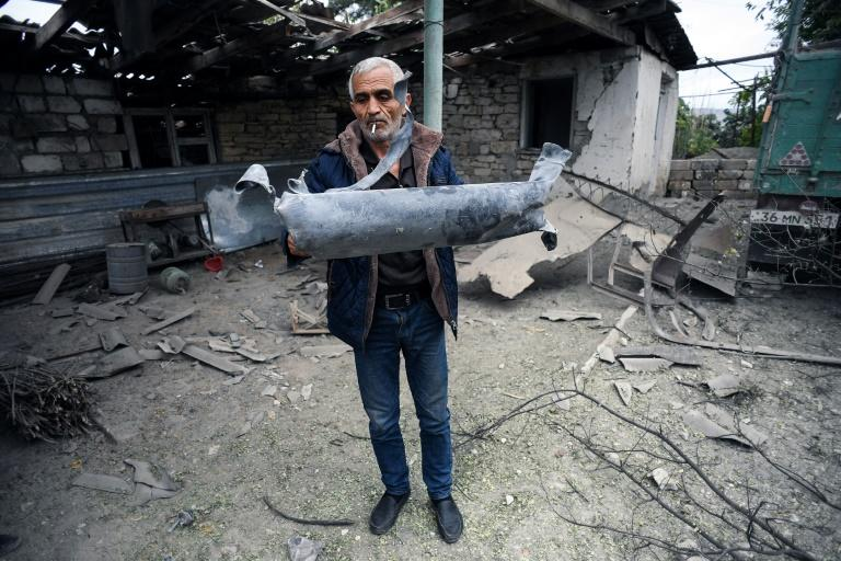 A man shows a shell fragment in the yard of a house damaged by shelling during fighting between Armenia and Azerbaijan over the breakaway Nagorny Karabakh region