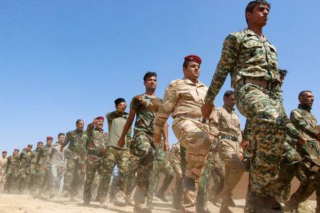 FILE PHOTO: Popular Mobilisation Forces (PMF) march during a military parade in Daquq, nearby Kirkuk, Iraq August 5, 2017. REUTERS/Ako Rasheed/File Photo