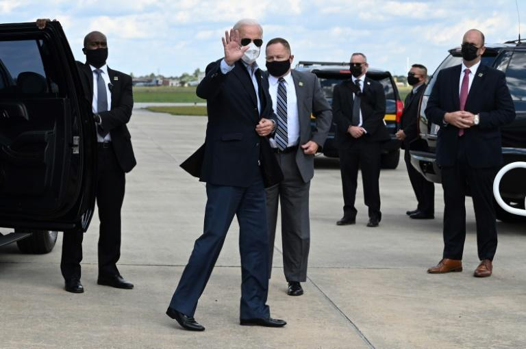 Joe Biden, seen here before boarding a plane for Michigan, is now alone on the campaign trail as Donald Trump recovers from a coronavirus infection