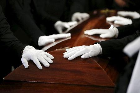 Pallbearers rest their hands on the casket of San Bernardino shooting victim Tin Nguyen during her funeral at Saint Barbara's Catholic Church in Santa Ana, California, December 12, 2015. REUTERS/Patrick T. Fallon -