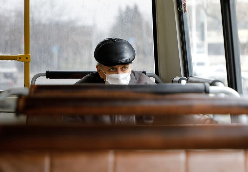 FILE PHOTO: A passenger wearing a protective mask sits inside a bus in Stavropol