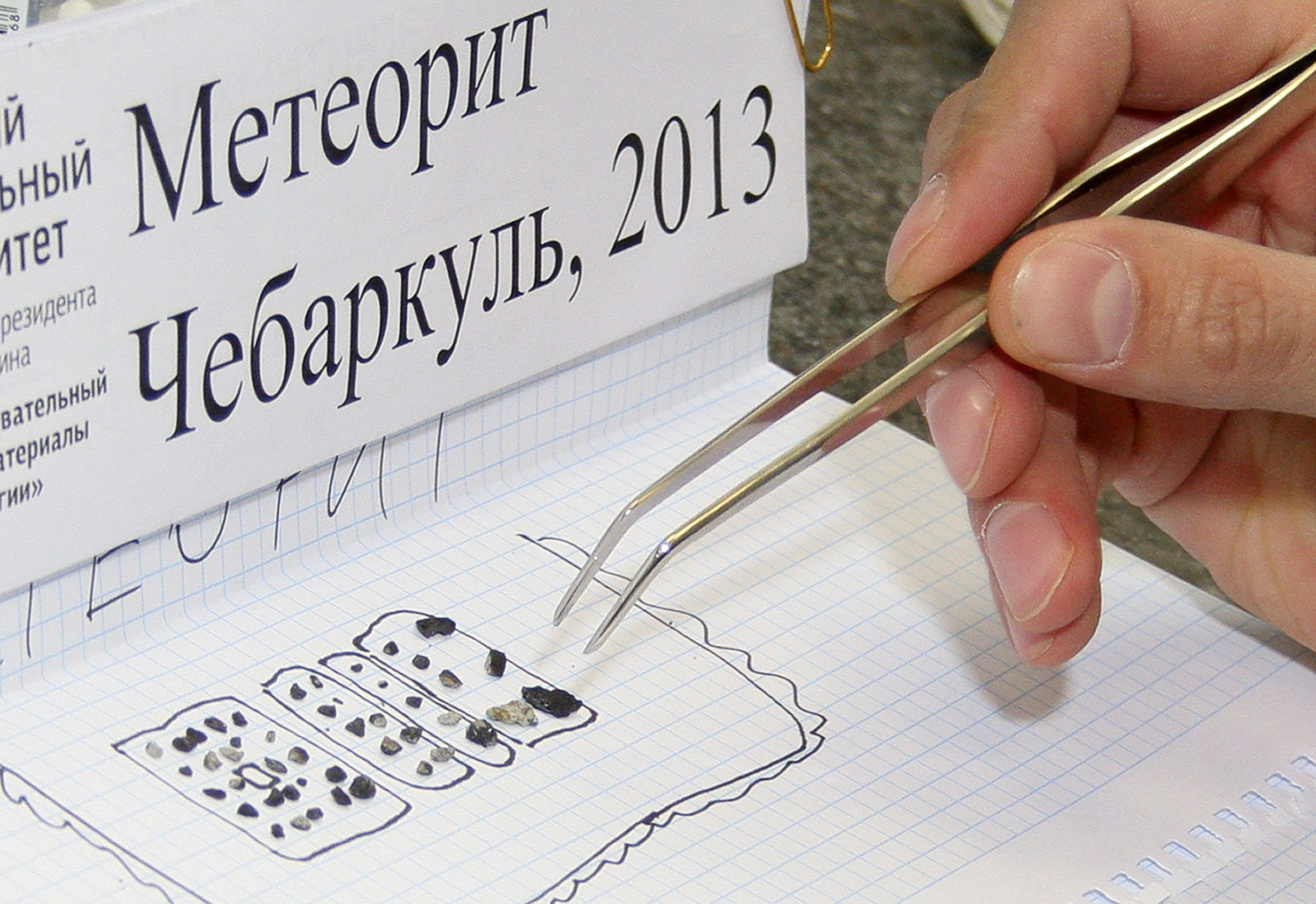 In this photo distributed by the Urals Federal University Press Service a researcher examines pieces of a meteorite in a laboratory in Yekaterinburg on Monday, Feb.18, 2013. Researchers from the Urals Federal University, based in Yekaterinburg, have determined that the small stone-like pieces found near Lake Cherbarkul in the Chelyabinsk region are pieces of the meteorite that exploded over the region Feb. 15. A total of 53 pieces have been brought for analysis to the university in Yekaterinburg. The largest one is one centimeter in diameter, the smallest is about one millimeter. It is written in Cyrillic: Meteorite Chebarkul. (AP Photo/ The Urals Federal University Press Service, Alexander Khlopotov)