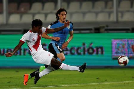 El jugador peruano Miguel Araujo y el uruguayo Edinson Cavani disputan el balón durante un partido disputado en Lima, Perú