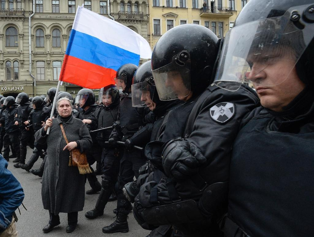 Riot police stand in line blocking access to an unauthorised anti-Putin rally in Saint Petersburg as a woman holding a Russian flag looks on (AFP Photo/Olga MALTSEVA )