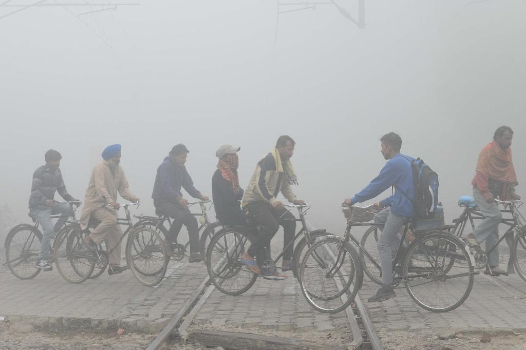 Indian commuters ride over tracks at a railway crossing amid heavy smog in Amritsar (AFP Photo/NARINDER NANU)