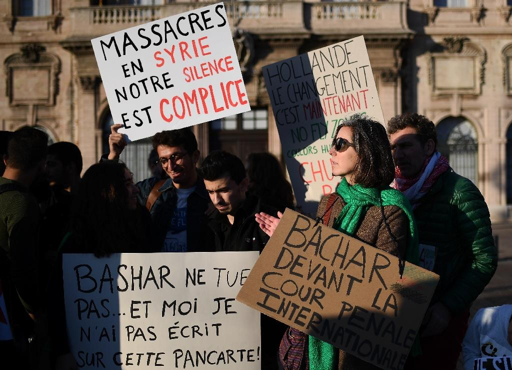 """Signs read """"Massacre in Syria, our silence is an accomplice"""" and """"Bachar to the International Criminal Court"""" during a protest in support of Aleppo's population in Marseille, France (AFP Photo/ANNE-CHRISTINE POUJOULAT)"""