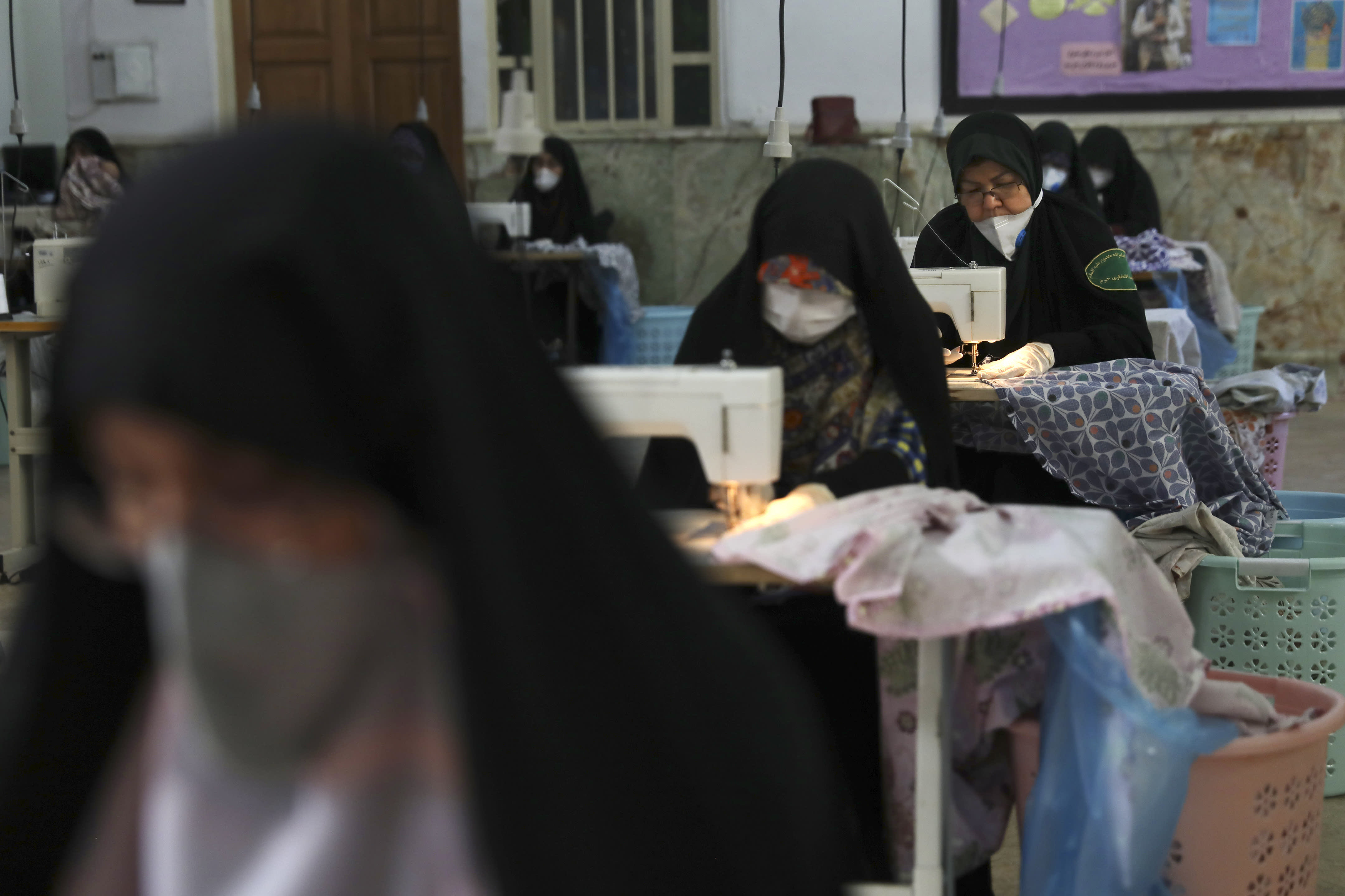 Volunteer women wearing face masks and gloves to curb the spread of the new coronavirus sew bed sheets for hospitals, in a mosque in southern Tehran, Iran, Sunday, April 5, 2020. Iran is battling the worst new coronavirus outbreak in the Mideast. (AP Photo/Vahid Salemi)