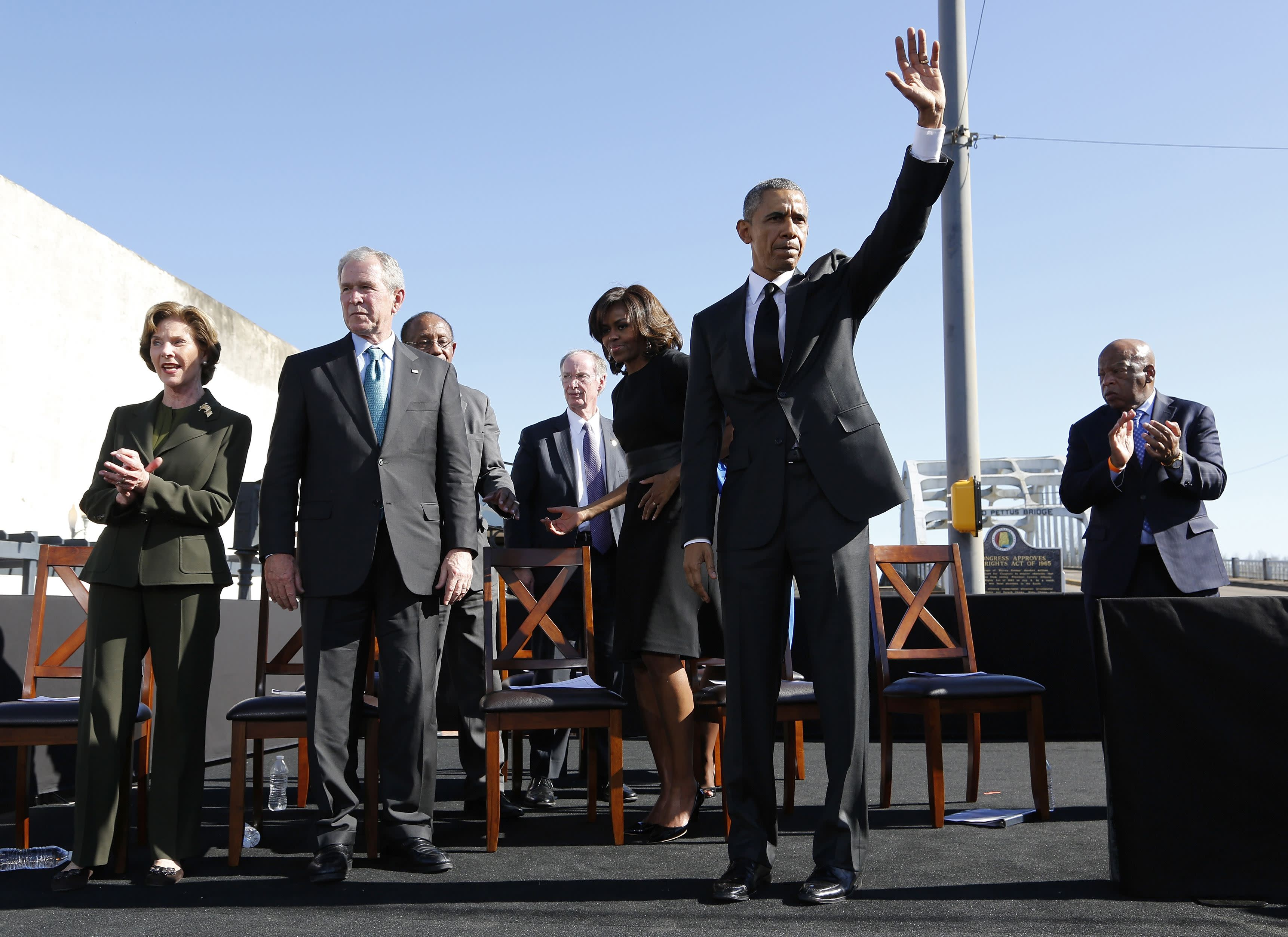 U.S. President Barack Obama (2nd R) acknowledges the crowd after remarks at the Edmund Pettus Bridge in Selma, Alabama, March 7, 2015. The remarks come on the 50th anniversary of the 'Bloody Sunday' march at the bridge, where police and state troopers beat and used tear gas against peaceful marchers who were advocating against racial discrimination at the voting booth. Also pictured are former first lady Laura Bush (L), former president George W Bush (2nd L) and first lady Michelle Obama (C). REUTERS/Jonathan Ernst (UNITED STATES - Tags: POLITICS ANNIVERSARY SOCIETY)
