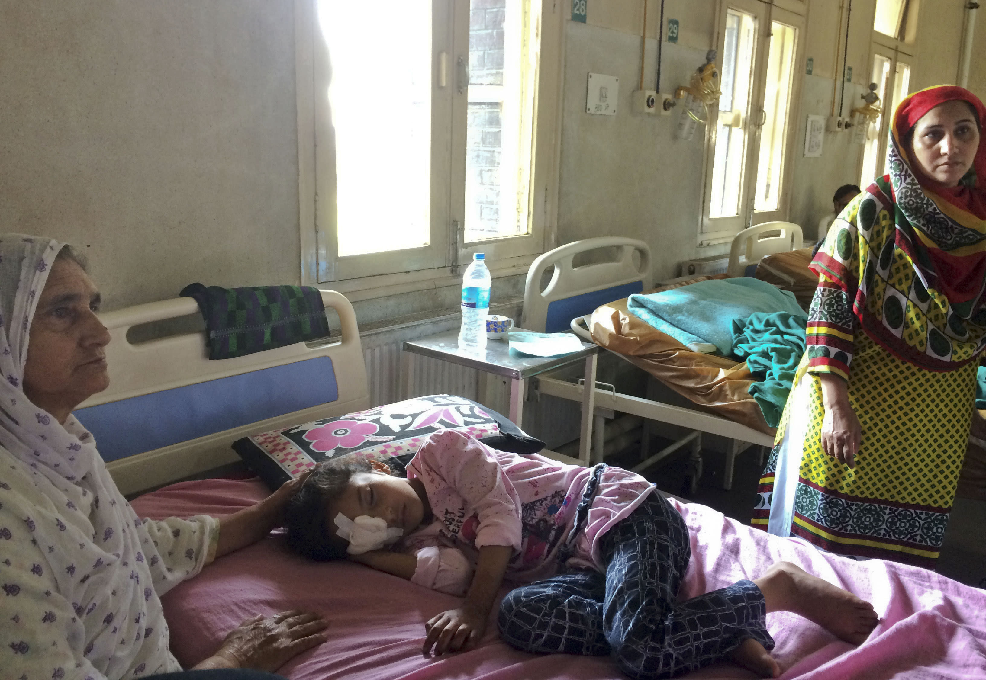 Grandmother Sara Ali, left, attends to six year old Kashmiri girl Muneefa Nazir, at a hospital after she was wounded by a marble shot from a sling used by Indian paramilitary soldiers in Srinagar Indian controlled Kashmir, Tuesday, Aug. 13, 2019. Indian Prime Minister Narendra Modi defended his government's controversial measure to strip the disputed Kashmir region of its statehood and special constitutional provisions in an Independence Day speech Thursday, as about 7 million Kashmiris stayed indoors for the 11th day of an unprecedented security lockdown and communications blackout. (AP Photo/ Aijaz Hussain)