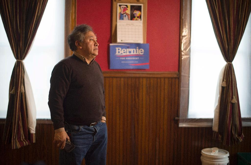 Present Captain of the local caucus Jose Zaharias stands in his living room near a Democratic Presidential Candidate Bernie Sanders placard in West Liberty, Iowa, January 25, 2016, ahead of the Iowa Caucus (AFP Photo/Jim Watson)