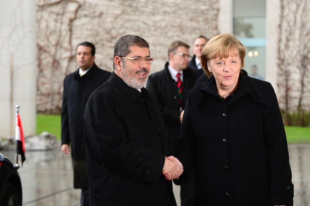 In this file photo taken in January 2013 German Chancellor Angela Merkel shakes hands with Egypt's then president Mohamed Morsi in Berlin (AFP Photo/John MACDOUGALL)
