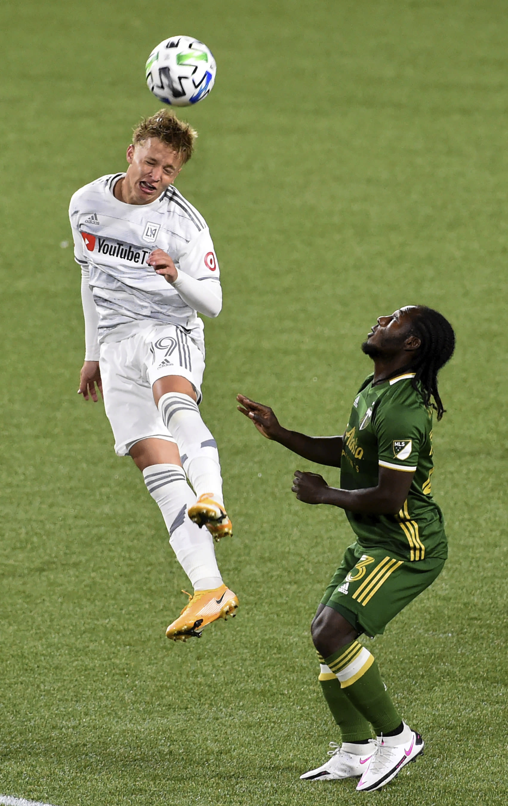 Los Angeles FC midfielder Bryce Duke, left, heads the ball away from Portland Timbers forward Yimmi Chara during the first half of an MLS soccer match in Portland, Ore., Sunday, Oct. 18, 2020. (AP Photo/Steve Dykes)