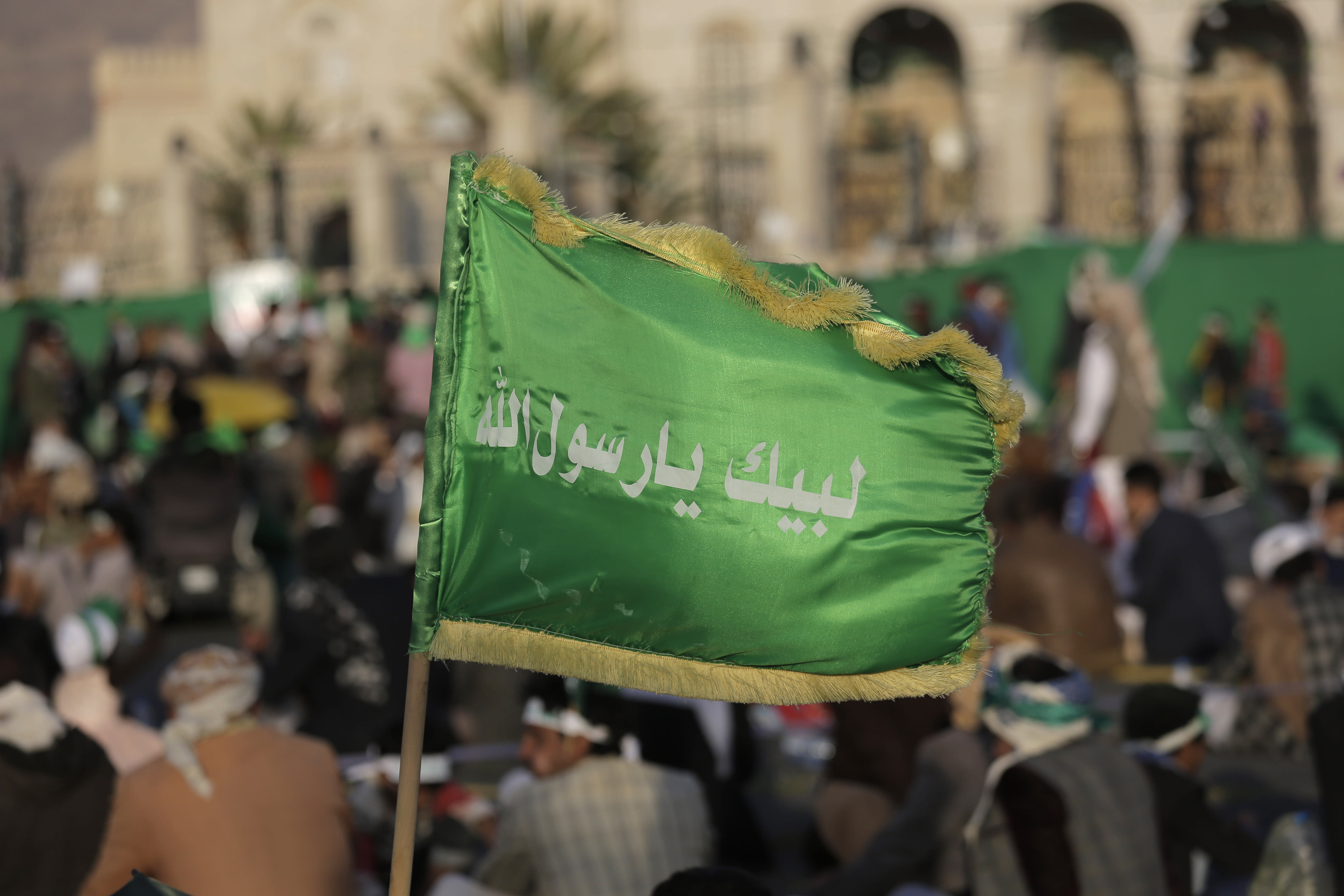 """FILE - In this Nov. 9, 2019 file photo, a supporter of Shiite rebels, known as Houthis, holds a banner with Arabic writing that reads, """"at your order, oh messenger of Allah,"""" during a celebration of Mawlid al-Nabi the birth of Islam's prophet Muhammad in Sanaa, Yemen. A satellite TV channel run by Yemen's Houthi rebels has broadcast on Thursday, Oct. 15, 2020, the start of a long-awaited prisoner exchange between the country's warring sides. (AP Photo/Hani Mohammed, File)"""