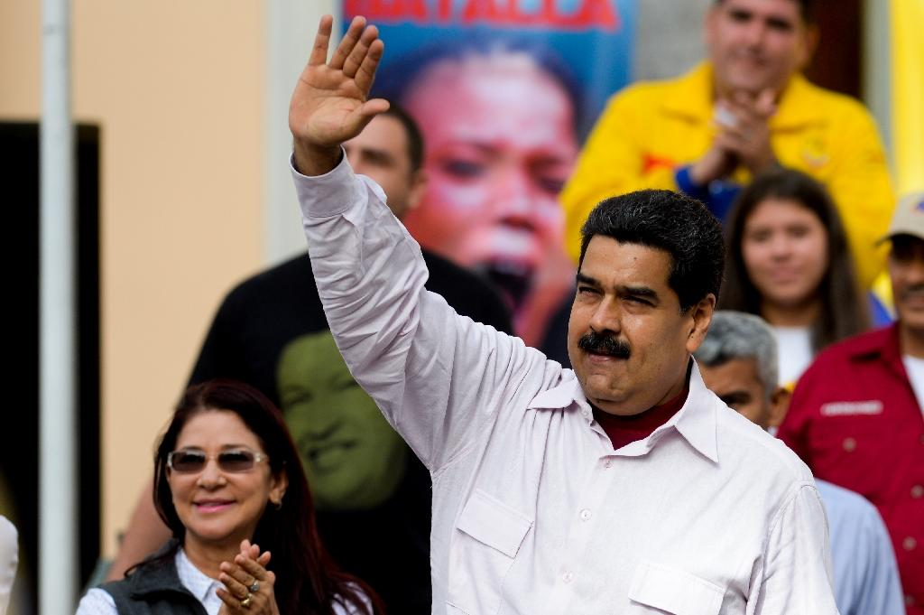 Venezuelan President Nicolas Maduro (R) greets supporters next to First Lady Cilia Flores during a rally in Caracas on June 14, 2016 (AFP Photo/Federico Parra)