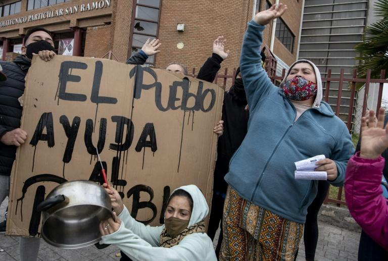 """Women bang pots next to a sign reading """"The people helps the people"""" to protest not getting aid during the coronavirus lockdown; the UN warns that 45 million people in Latin America and the Caribbean could fall into poverty because of the pandemic"""