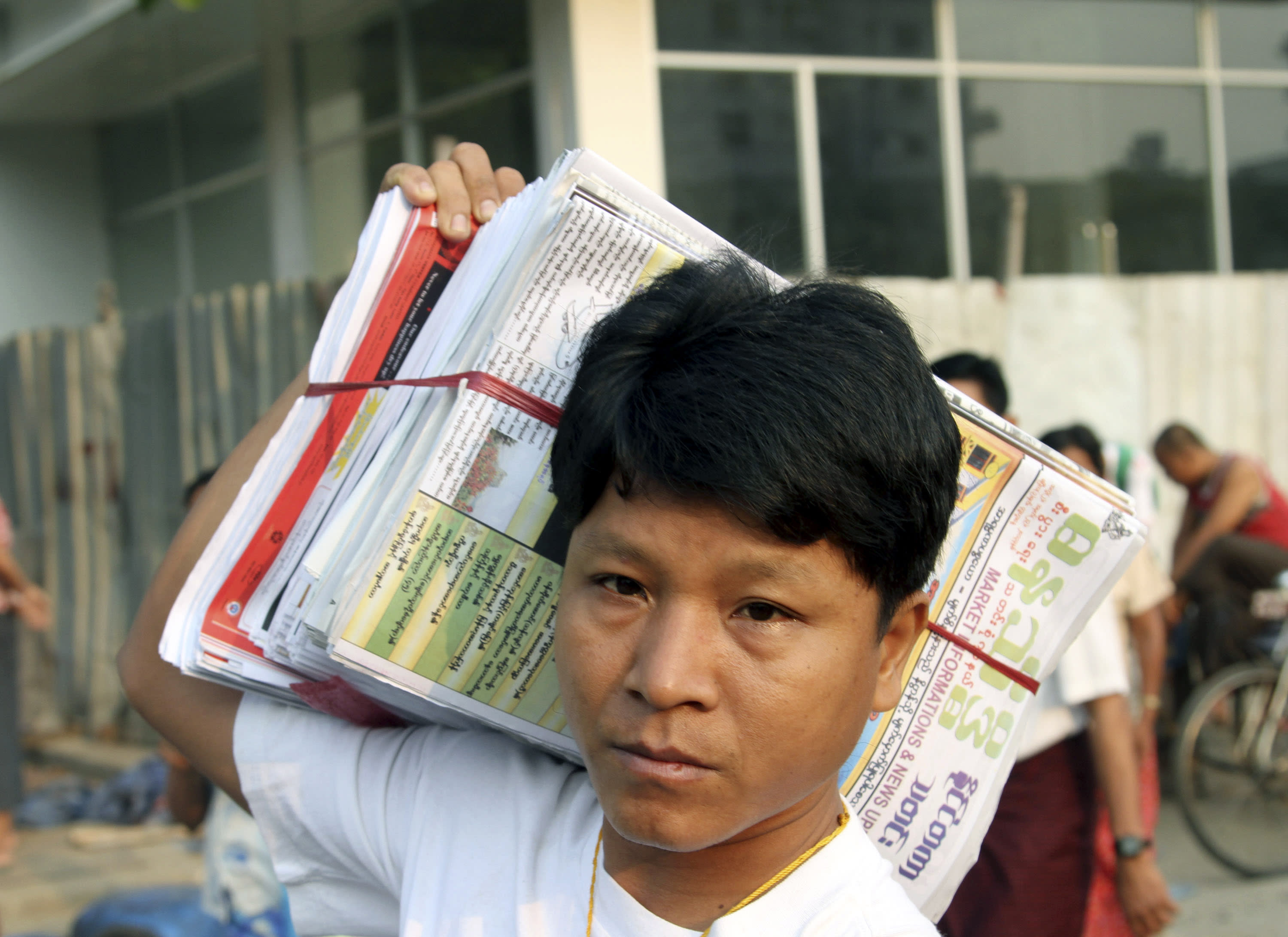 A man carries daily newspapers on his shoulder to sell at his roadside shop Monday, April 1, 2013, in Yangon, Myanmar. For most people in Myanmar, it will be a novelty when privately run daily newspapers hit the streets on Monday. Many weren't even born when the late dictator Ne Win imposed a state monopoly on the daily press in the 1960s. (AP Photo/Khin Maung Win)