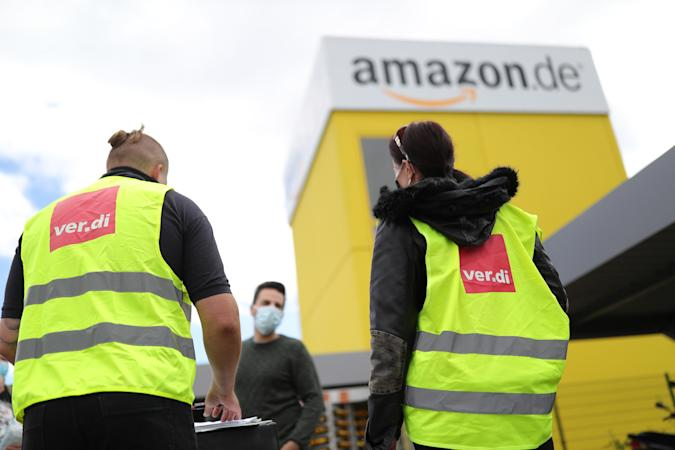 KOBERN-GONDORF, GERMANY - JUNE 29: Striking Amazon employees stand outside an Amazon warehouse during the coronavirus pandemic on June 29, 2020 in Kobern-Gondorf near Koblenz, Germany. The Verdi labor union has called for strikes at six Amazon warehouse across Germany in order to put pressure on the company over an ongoing disagreement over pay as well as improving workplace conditions to help prevent outbreaks of the coronavirus. Approximately 40 Amazon employees tested positive recently for Covid-19 infection at an Amazon warehouse in Bad Hersfeld. (Photo by Andreas Rentz/Getty Images)
