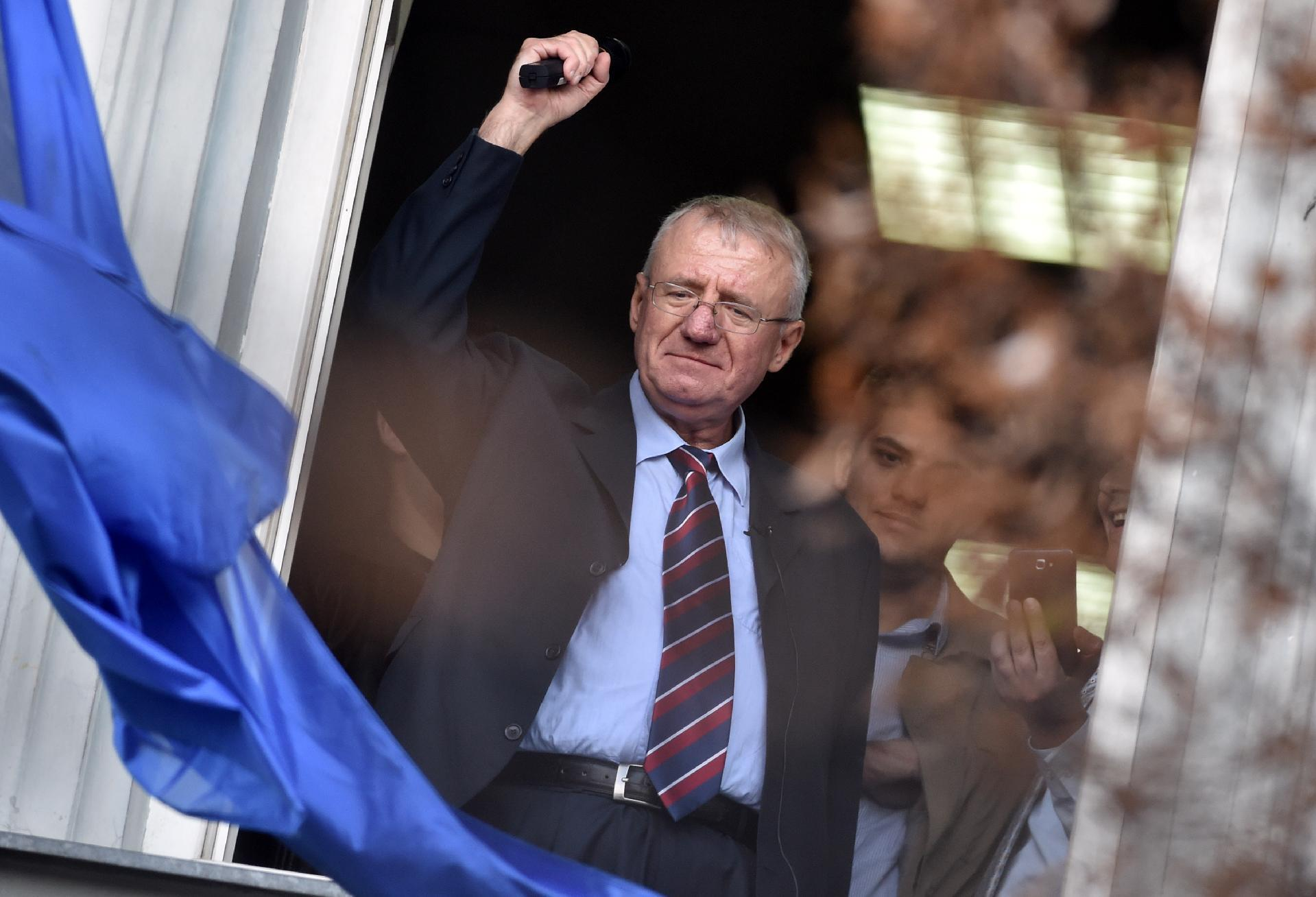 Serb ultranationalist leader Vojislav Seselj waves at supporters on November 12, 2014 after arriving at his Radical Serb Party (SRS) headquarters in Zemun, near Belgrade