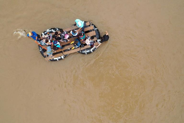 Guatemalan migrants likely headed for the United States use a raft to cross the Suchiate river from Guatemala into Mexico in July (AFP Photo/ALFREDO ESTRELLA)