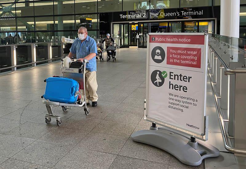 A passenger walks through a terminal at Heathrow Airport, as Britain launches its 14-day quarantine for international arrivals, following the outbreak of the coronavirus disease (COVID-19), London, Britain