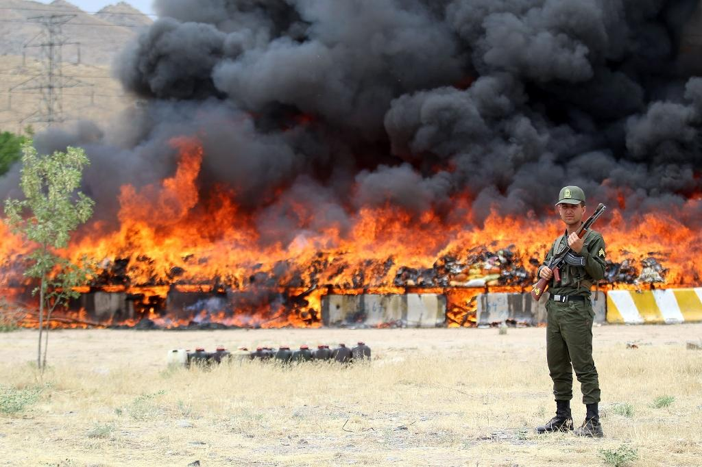 An Iranian policeman stands guard as 50 tonnes of illegal drugs are destroyed on June 27, 2015 in the northeastern city of Mashhad