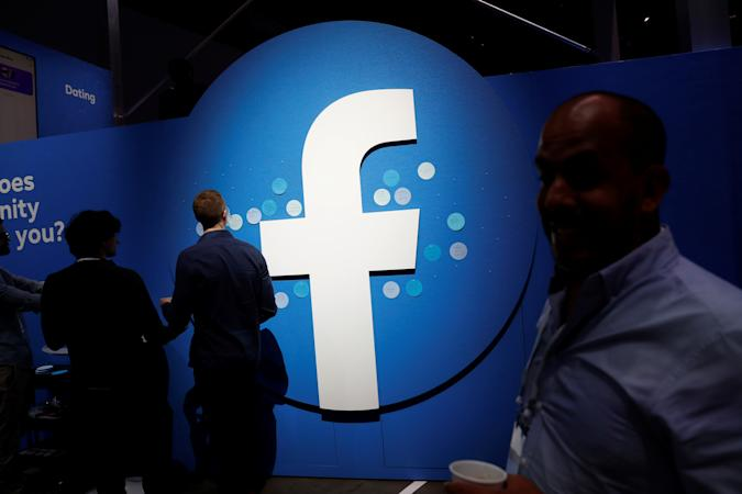 Attendees walk past a Facebook logo during Facebook Inc's F8 developers conference in San Jose, California, U.S., April 30, 2019.  REUTERS/Stephen Lam