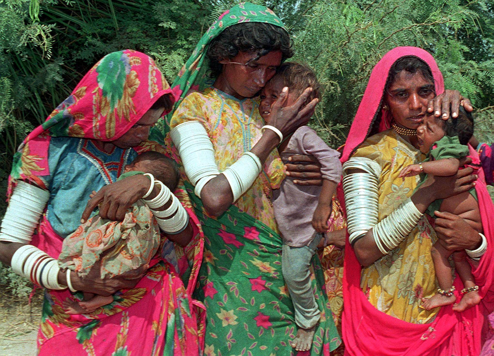 Three freed women slaves hug their children after being rescued by authorities as they arrive in the town of Matli, northeast of Karachi, Pakistan, on September 13, 1998 (AFP Photo/Yousuf Nagori)