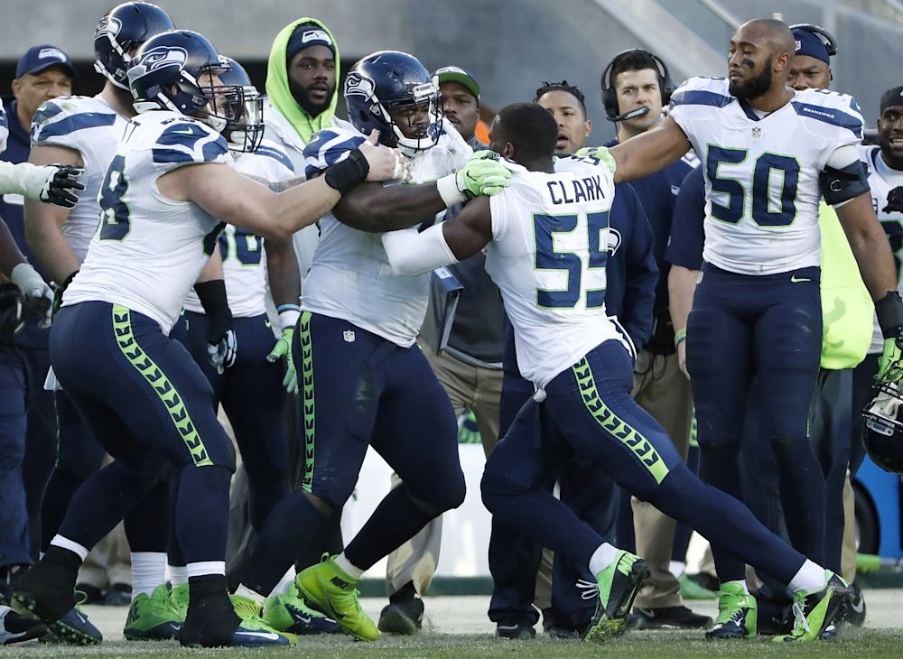 Frank Clark isn't shy in getting physical with teammates, evidenced in this shoving match he got into with teammate Jarran Reed during a game last season against the 49ers. (AP)
