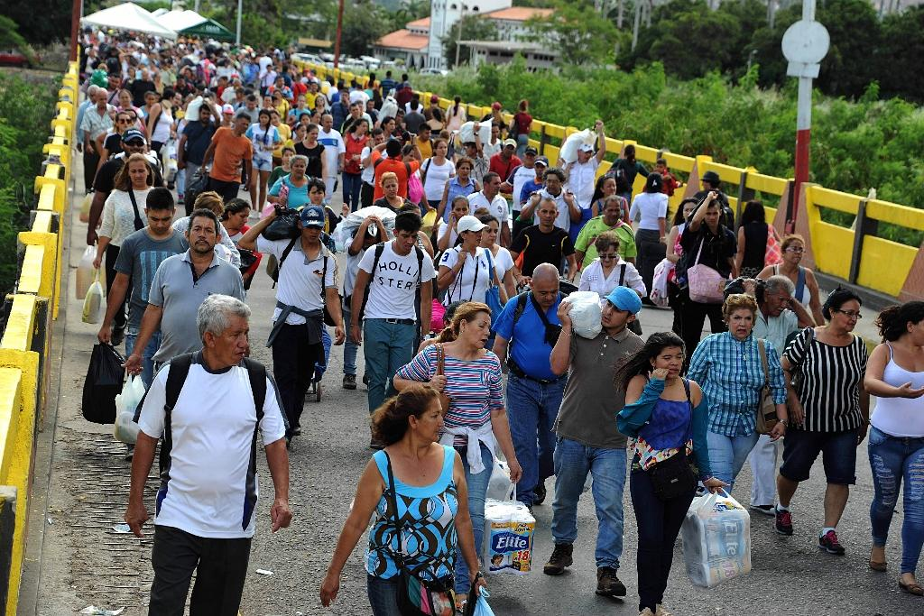 Venezuelans carrying groceries cross the Simon Bolivar bridge from Cucuta in Colombia back to San Antonio de Tachira in Venezuela, on July 17, 2016 (AFP Photo/George Castellanos)