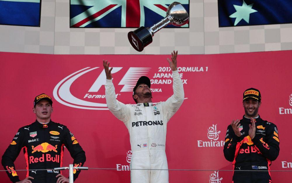 Lewis Hamilton (C) celebrates winning the Japanese Grand Prix - AFP